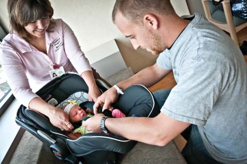 Nicole Capozello, a certified car seat safety technician, shows a first-time dad at Beaumont Hospital, Troy how to properly buckle up his baby girl.