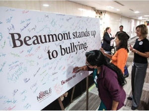 Marlene Seltzer, M.D., (far right) looks on as team members sign an anti-bullying poster at Beaumont Hospital, Royal Oak in early October.