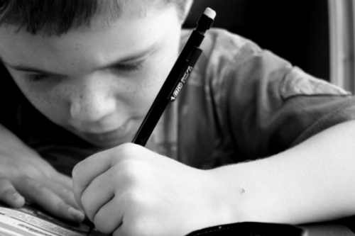 Up close photo of boy writing