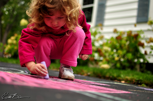 Little girl using sidewalk chalk