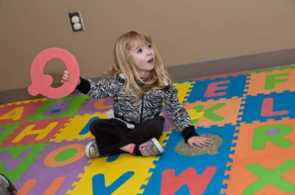 Girl on floor puzzle holding a letter.
