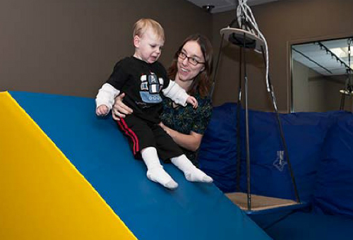 Therapist holding a child on foam slide.