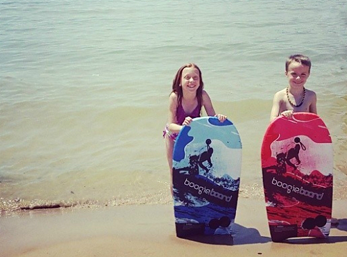 Girl and boy with boogie boards in Lake Michigan