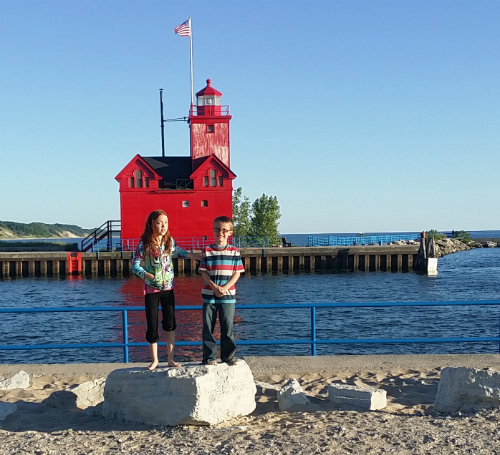Girl and boy standing on a rock in front of a red lighthouse