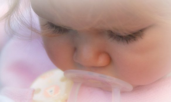 Close up of young girl sucking on pacifier