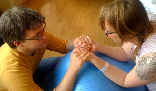 Dad holding mom's hands over birthing ball