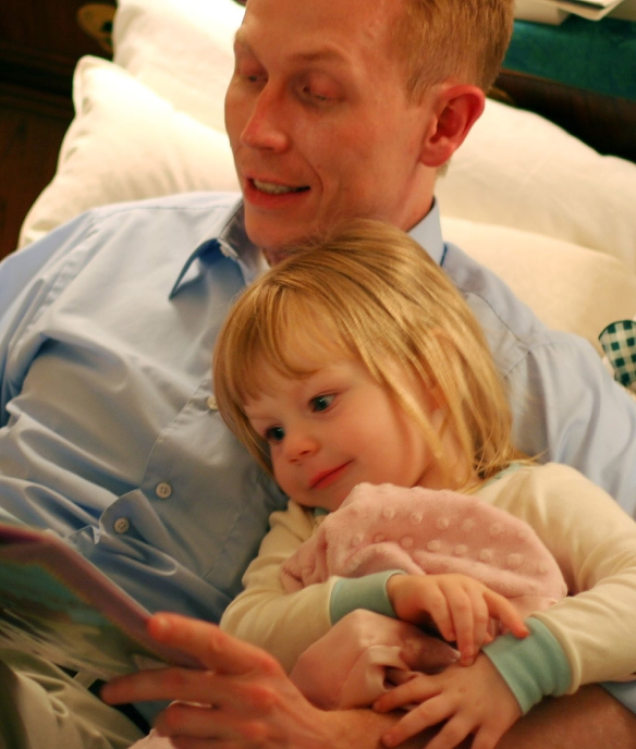 Dad reading a bedtime story to his daughter.