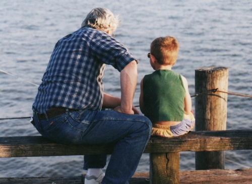Grandpa and boy sitting on a dock look out at the water
