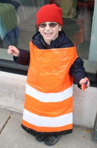 Boy dressed as a construction barrel for Halloween