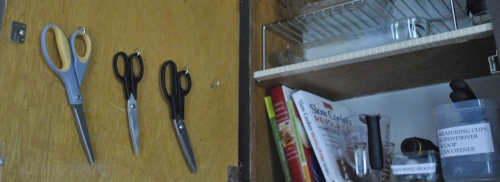 Scissors hanging inside a cabinet door