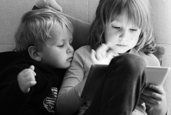 Older girl using iPad while little boy watches.
