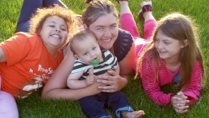 Woman and three kids lying on the grass.