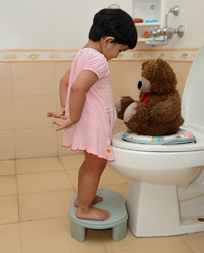 Little girl potty training her teddy bear