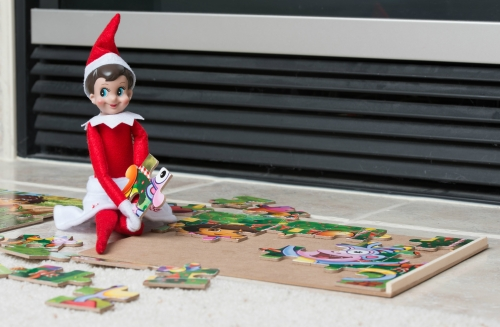 Elf on the shelf doing a puzzle