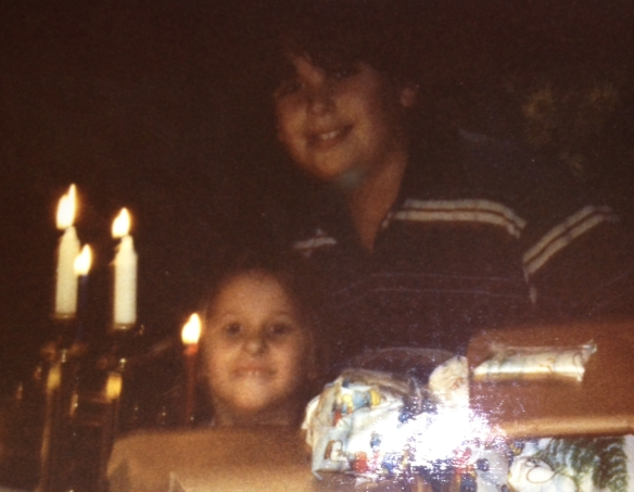 A boy and girl behind a menorah