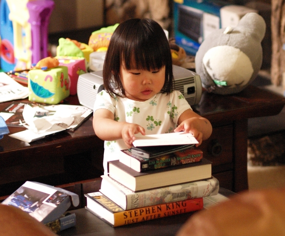 Little girl stacking books