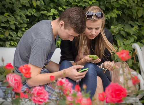 A teenage couple using cell phones