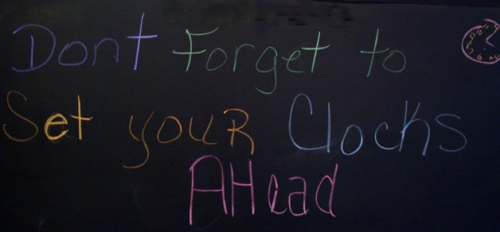 """Don't forget to set your clocks ahead"" written on chalkboard"