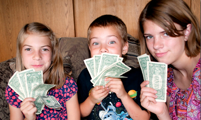 2 girls and 1 boy holding dollar bills