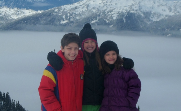 Boy and two girls in snowy mountains
