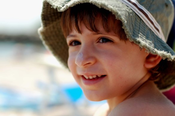Boy wearing a hat with sunscreen on nose
