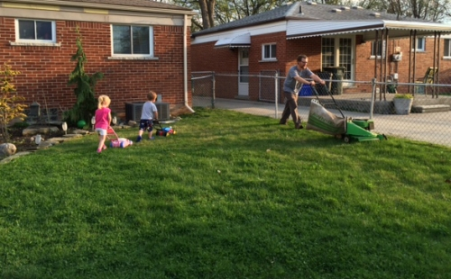 Two children mowing the lawn behind dad