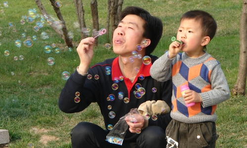 Father and toddler son blowing bubbles together