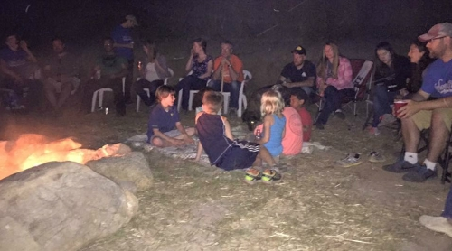 Kids and adults around a large campfire