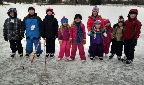 A bunch of kids standing on a frozen, outdoor pond