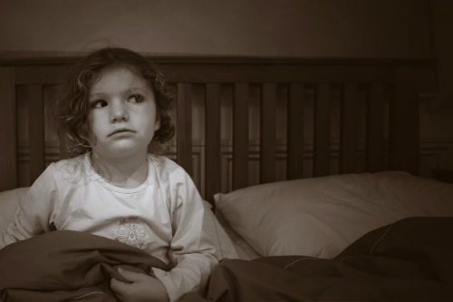 Scared little girl sitting up in bed