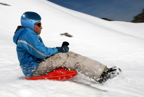 Boy sledding wearing a helmet