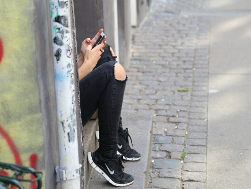 Hidden girl sitting in doorway playing with cell phone