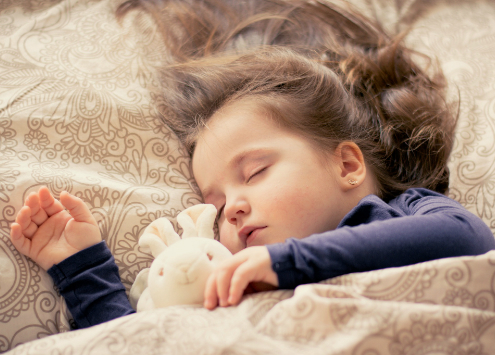 Young girl sleeping with stuffed bunny