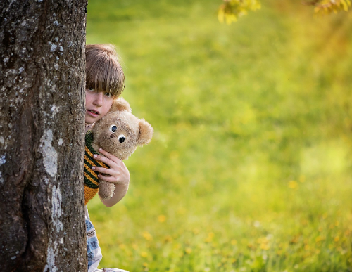 Girl holding teddy bear peeking out from behind a tree