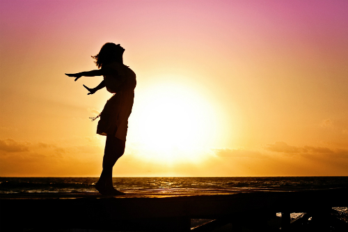 Silhouette of woman standing on beach against a sunrise