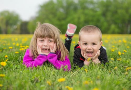 Boy and girl laying in field of dandelions