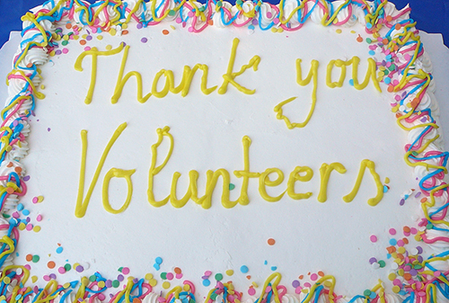 "Cake with ""Thank you volunteers"" written on it"