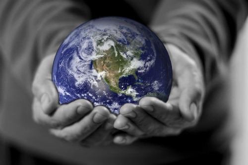 Black & white hands holding color Earth