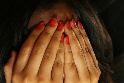 Close up of woman covering her face with her hands