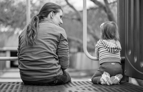 Mom and daughter sitting on playground equipment
