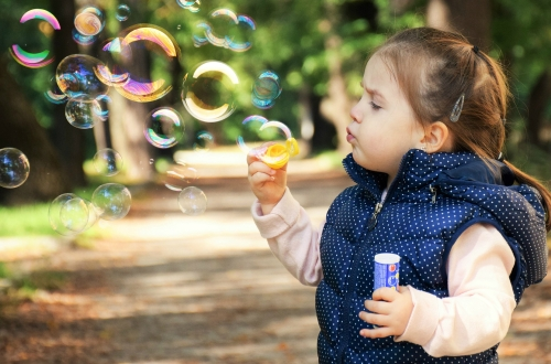 Little girl blowing bubbles outside