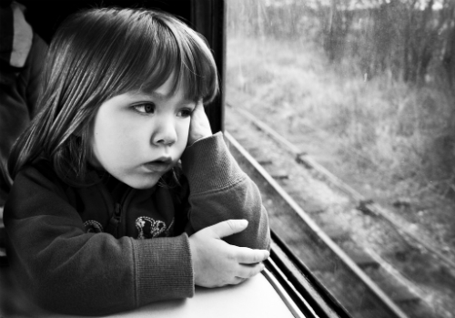 Little girl looking out a train window