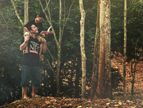 Boy on his dad's shoulders in the woods