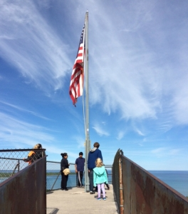 People looking out at the water with an American flag