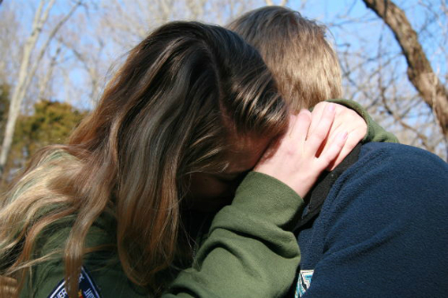 Young girl crying on shoulder of a young man