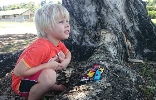 Little boy playing with his cars by a tree