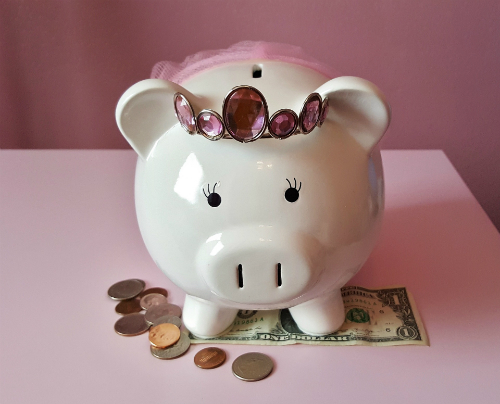 Piggy bank, wearing tiara, standing on dollar and coins