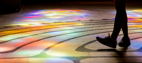 Close up of feet walking on a colorful lit floor