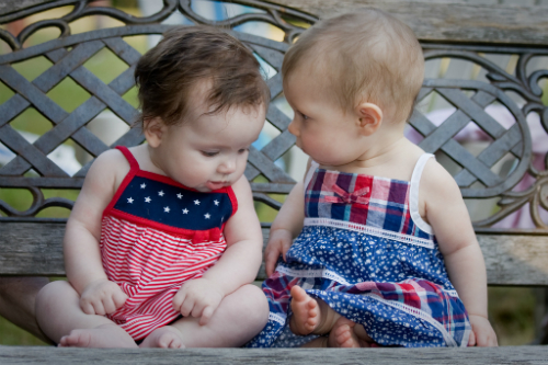 "Two baby girls ""talking"" on a bench"