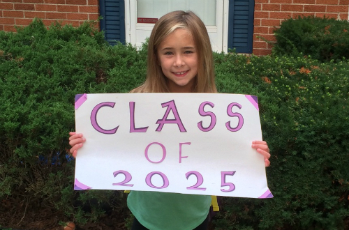 "Young girl holding a ""Class of 2025"" sign"